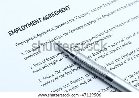 Close-up of silver pen on employment agreement. Selective focus on top of pen. Toned monochrome image. - stock photo