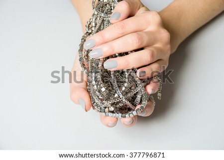 Close up of single Caucasian hand holding bundle of necklaces