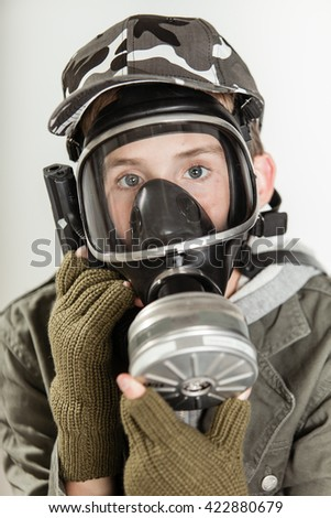 Close up of single male teen in jacket, brown gloves and gray camouflage hat holding a visor respirator gas mask on his face - stock photo