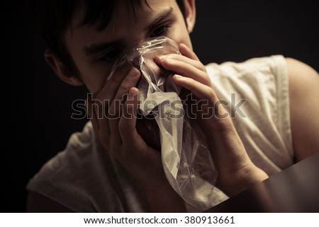 Close up of single male teenager inhaling narcotics from plastic resealable bag on his mouth - stock photo