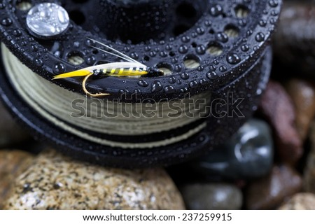 Close up of single trout fly, focus on golden barbed hook with shallow depth of field, on wet fishing reel with blurred out river rocks in background - stock photo