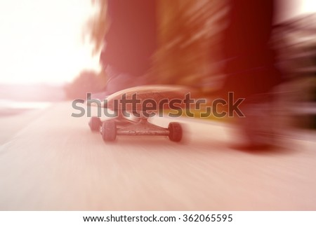 Close up of skateboarder and skateboard with motion blur and strong lens flare effect. - stock photo