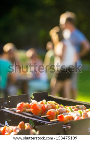 Close-up of skewers grilling on barbecue at garden party - stock photo