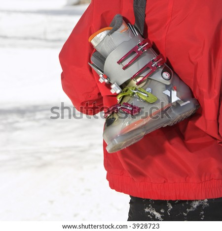 Close up of ski boot hung over shoulder of shoulder of male teenager. - stock photo