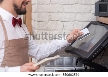 Close up of skillful male cafe worker is swiping credit card through the screen. He is holding a checkbook and smiling - stock photo