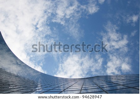 close-up of skyscraper against cloudy  sky ; abstract office building glass background - stock photo
