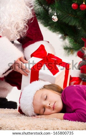 Close up of sleeping little girl under Christmas tree. Santa Clause putting present in a box behind girl head  - stock photo