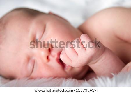 Close up of sleeping newborn babys hand. Focused on hand - stock photo