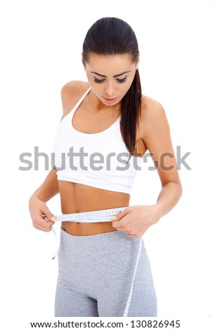 Close-up of slender woman measuring her waist over white background