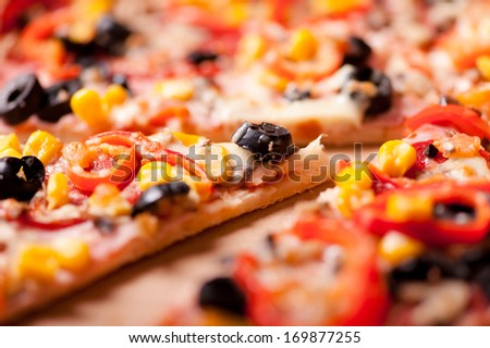 Close-up of slice of dinner pizza with ham, olives, mozzarella, pepperoni and tomatoes