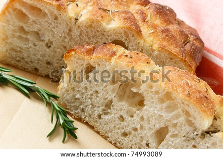 Close up of sliced artisan focaccia bread with a sprig of rosemary - stock photo