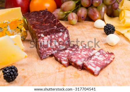 Close Up of Sliced Cured Meat on Gourmet Cheese Board with Variety of Cheeses and Garnished with Fruit - stock photo