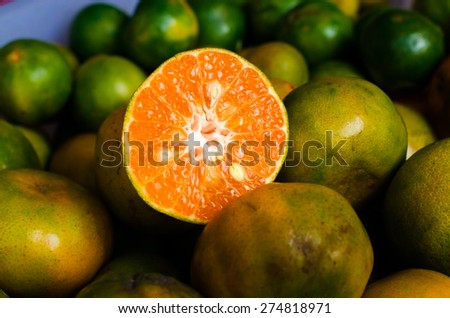 Close up of Sliced oranges on a market/ Close up of sliced thai green oranges on a market/ Thai oranges stack on the market for sale (fruit, orange, juicy) - stock photo