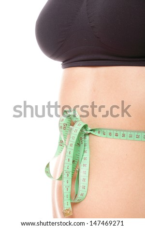 Close-up of slim stomach with measuring tape around it Woman body part is being measured - stock photo
