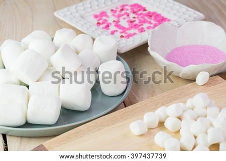 Close up of small and large marshmallows, pink sugar, sprinkles - ingredients for easter bunny cake decoration. - stock photo