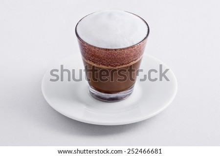 close up of small coffee cup with milk on white background - stock photo