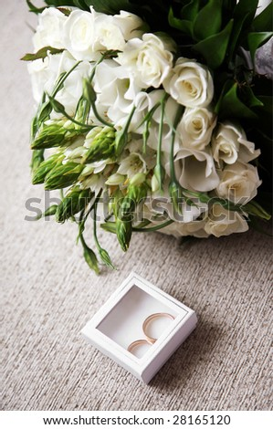 Close-up of small decorative box with two wedding rings near rose bouquet - stock photo