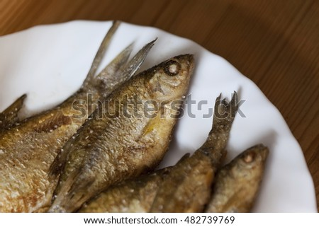Close up of small fried fishes on a white plate in a kitchen