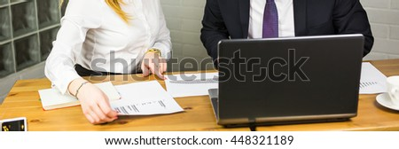 Close-up of smart business partners using laptop at meeting - stock photo