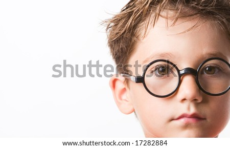 Close-up of smart guy in preschool age looking at camera through glasses - stock photo