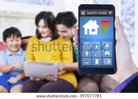 Close up of smart home application on the mobile phone, shot with happy family using tablet at home - stock photo