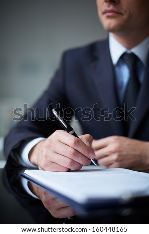 Close-up of smart male hands with pen over document - stock photo