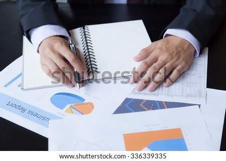 Close-up of smart male hands with pen over document