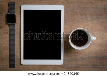 Close up of smartphone and smartwatch with coffee cup on wooden table