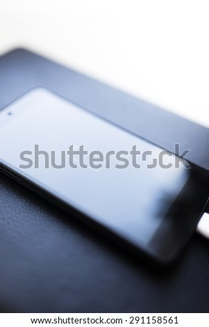 Close-up of smartphone with low battery symbol on charge