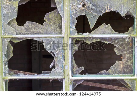 Close up of smashed reinforced panes of glass in a window in a delapidated building - stock photo