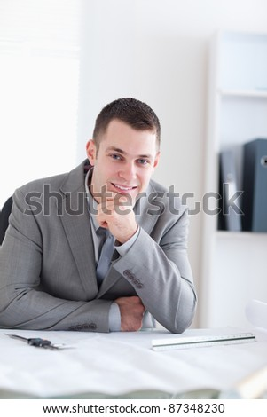 Close up of smiling and thinking architect sitting behind a table