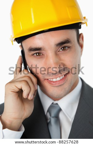 Close up of smiling architect talking on the phone against a white background