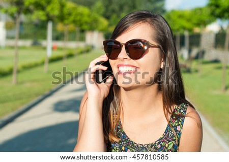 Close-up of smiling attractive girl talking at telephone outside in park on sunny day wearing sunglasses with copy text space - stock photo