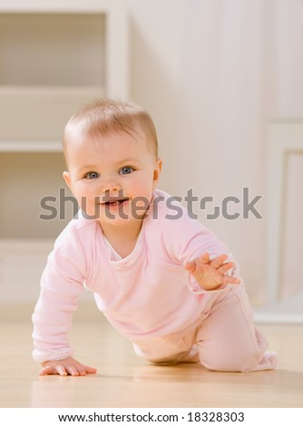 Close up of smiling baby crawling on livingroom floor [Approx. 8 mos] - stock photo