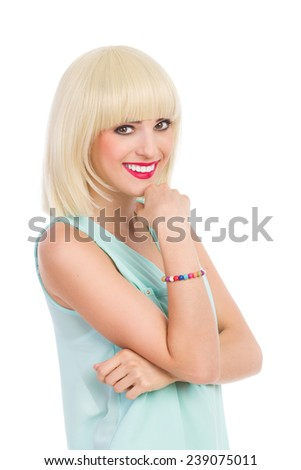 Close up of smiling beautiful blond young woman looking at camera and holding hand on chin. Waist up studio shot isolated on white. - stock photo