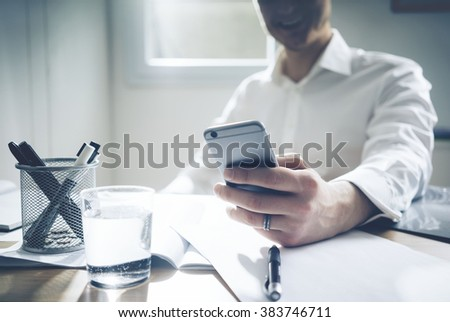 Close up of smiling businessman sitting at his office and using modern smart phone, documents and glass of water on desk  - stock photo