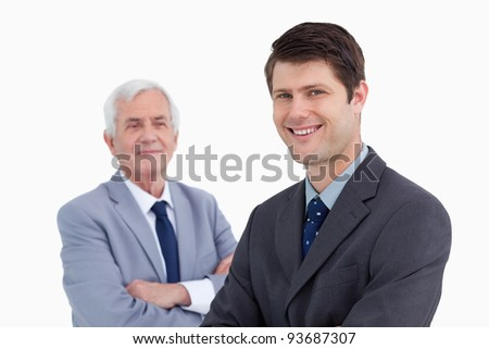Close up of smiling businessman with his mentor behind him against a white background - stock photo