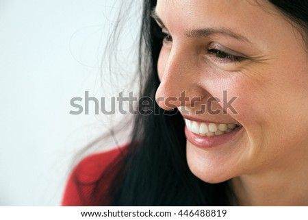 Close-up of smiling candid and cheerful adult woman looking away - stock photo