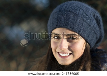 close up of smiling cute girl with winter hat. outdoor shot with unfocused blurred background. - stock photo