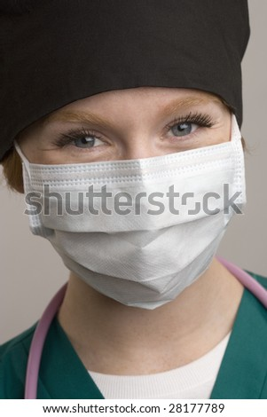 Close up of smiling female medical staff wearing surgical mask - stock photo