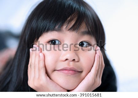 Close-up of smiling girl with hand on chin. - stock photo