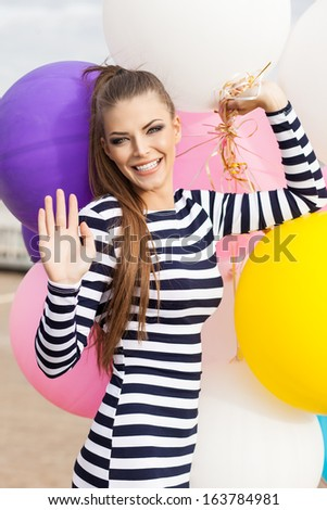 close-up of smiling girl with smokey eye make up and long hair in black and white striped dress waves holding bunch of multicolored balloons - stock photo