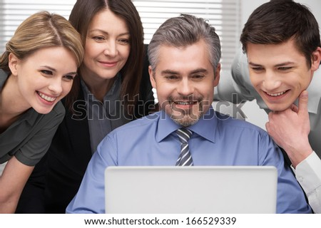 Close up of Smiling group of people looking at laptop. Looking happy and successful sitting in modern office