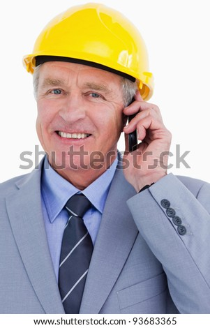 Close up of smiling mature architect on his cellphone against a white background