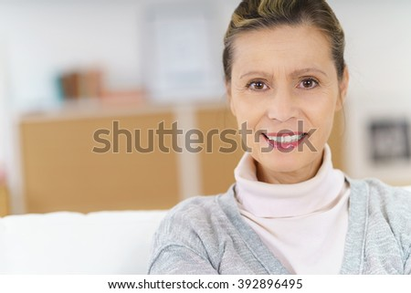 Close up of smiling middle aged woman looking at camera as she sits on sofa next to copy space