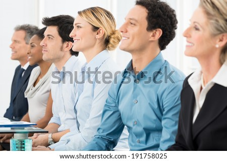 Close Up Of Smiling Multiracial Businesspeople Sitting In A Row - stock photo