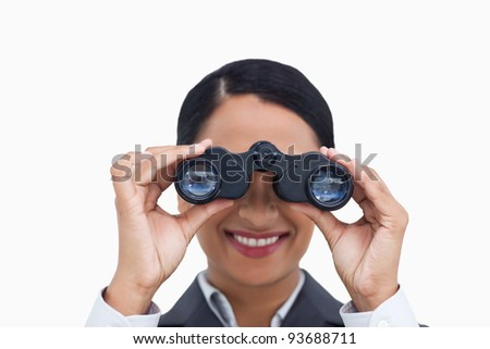 Close up of smiling saleswoman using spy glasses against a white background - stock photo