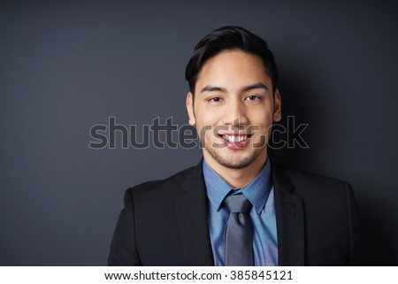 Close up of smiling single young bearded male manager in blue jacket, shirt and necktie with copy space in dark background - stock photo