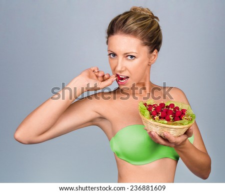 Close up of smiling woman holding raspberries isolated on white - stock photo