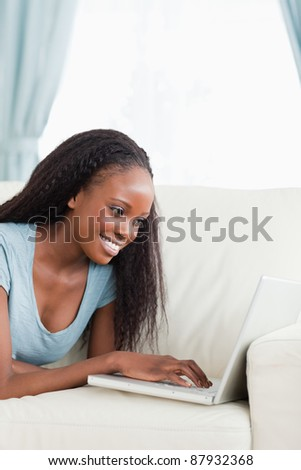 Close up of smiling woman lying on the sofa working with her notebook